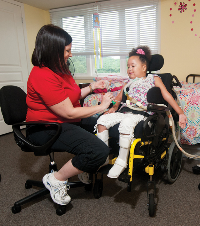 nurse administering IV in young patient on a wheelchair